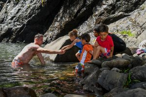 Dad and children swim in the river at Family vacation