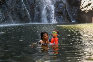 Mom and son swim in the river against the waterfall in Fiji