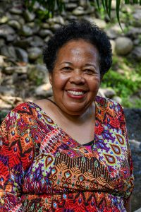 Portrait of polynesian grandma smiles at the camera in family vacation photoshoot