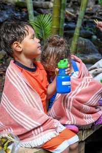 Triplets snack together by the river in Fiji family vacation