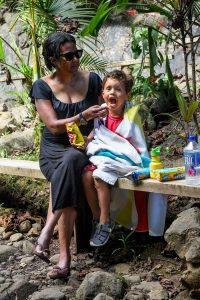 Mom feeds son against the river in Fiji family vacation