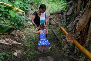 Mom carries daughter over rock in Fiji rainforest