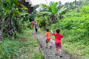Triplets run back up the road in Fiji tropical rainforest