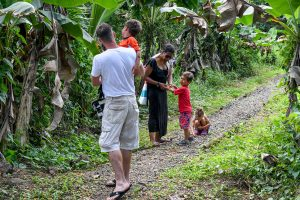 Family walks down the road in Tropical rainforest in Fiji family vacation