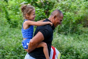 Girl rides piggyback on grandpa in Fiji