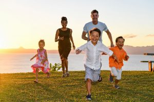 Family runs against ocean and sunset in Fiji family photo shoot