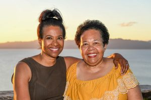 Mom and daughter hug against sunset in Fiji
