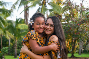 Mother and daughter cuddle with lofty green palm trees towering behind them