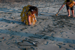 The family draws their name in the sand