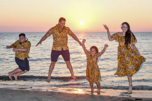 The family leaps against a golden sunset at Double Tree Hilton