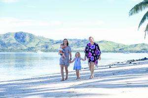 same-sex family strolling down the beach at Plantation Island Resort