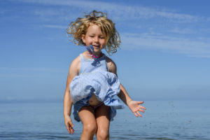 Cute girl jumps into the air in the sea