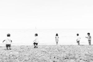 Monochrome photo of toddlers waddling on the beach