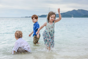 Brother's and sisters play in the sea