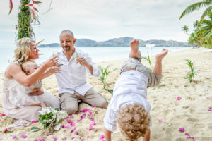 Newly married couple drink champagne as their children play in the sand