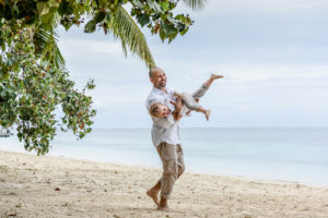 Dad carries his son in the air while on the beach in Fiji