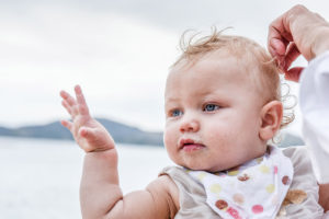 Cute blue-eyed baby on the beach