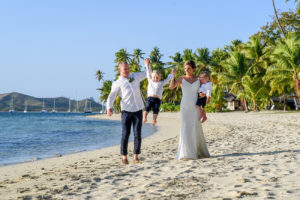 Mom and dad lift their son in all white family photoshoot in Fiji