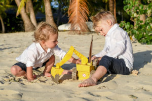 Siblings build sand castles in the sand