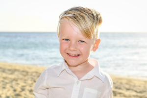 blond green-eyed boy in the sand