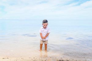 Cute baby boy watching fish in clear Fiji sea against stunning baby blue sky