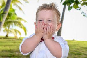 Cute shy baby boy with palm trees in Fiji