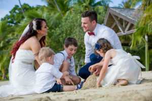 Newly married couple build sand castles with their babies in the sand