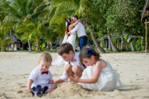 Newly married couple kiss in the background as children play with sand castles on the shore