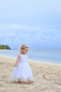 Stunning baby girl in all white strolling on Fiji water