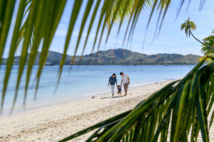 Palm tree fronds frame the couple as they have a stroll on the beach at Plantation Island Resort Fiji
