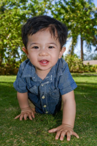 The cute little boy crawls on the green lawn at Plantation Island Resort towards the camera
