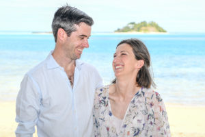 The happy couple laugh while standing at the stunning beach at Malolo Island
