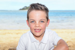 The cute blue eyed boy on the sunny beach at Malolo Island