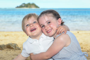 The sister hugs her cute little brother while seated on the warm sandy beaches at Malolo Island