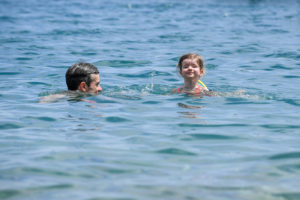 The baby paddles with her father in the ocean