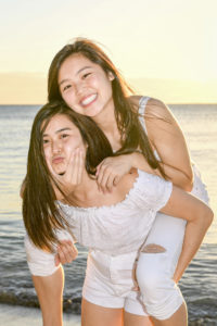 Asian sisters goof on the beach in the sunset