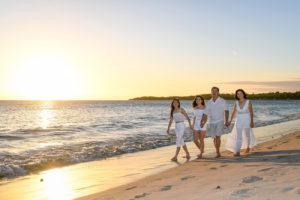 The family strolls beside the golden Fiji sunset