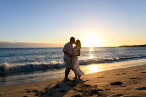 An asian couple kisses against the sunset