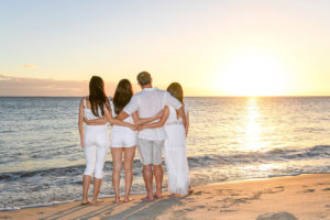 The family hold hands as they watch the golden Fiji sunset