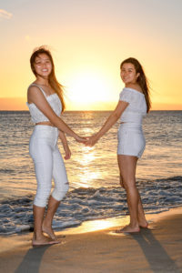 Sisters hold hands against the fiery Fiji sunset