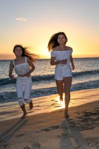 Asian sisters run on the beach against the setting Fiji sun