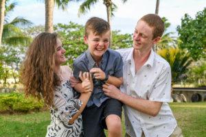 A boy laughs as his cousins tickle him