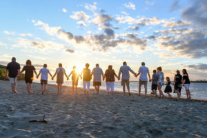 Extended family members hold hands as they walk towards the sunset at Natadola beach