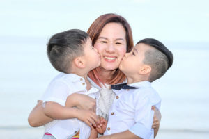 Two sons kiss their mother on the cheek