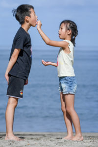 A sister feeds her brother with the Pacific ocean in the background