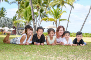 Asian siblings pose on the manicured grass at Natadola Fiji