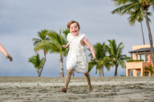 A happy boy leaps and jumps on the beach against palm trees at Natadola beach
