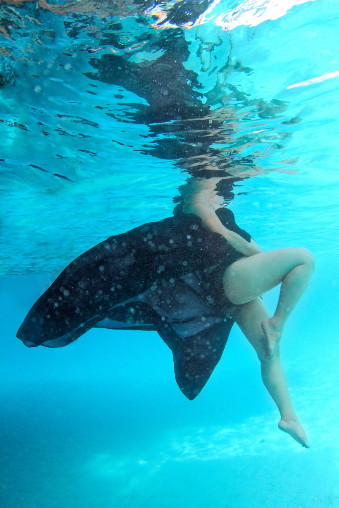 A black dress floats behind the legs of a pregnant lady floating underwater
