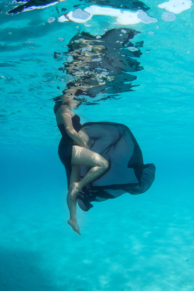 Lady holds baby bump as she floats underwater with her black dress flowing around her