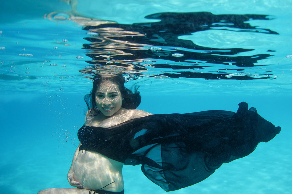 Pregnant underwater mermaid smiles at the camera as she floats underwater